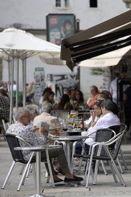 Varias personas en la terraza de un bar en Galicia.