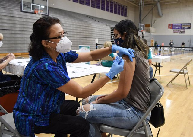 11 September 2021, US, Winter Springs: Nurse Susanna Bryan (L)administers a dose of the Pfizer COVID-19 vaccine to Joann Cortes at a vaccination clinic at Winter Springs High School. As of 10 September 2021, 54\% of Florida's population has been fully va
