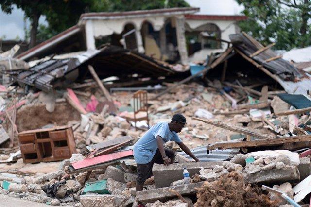 Archivo - Un hombre busca entre los escombros tras el terremoto en Les Cayes, Haití