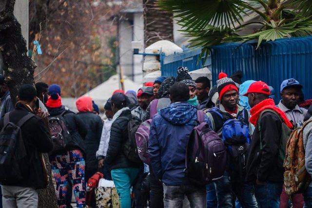 Archivo - Migrantes de Haití esperan frente a la embajada de su país en Santiago para resolver su situación migratoria.