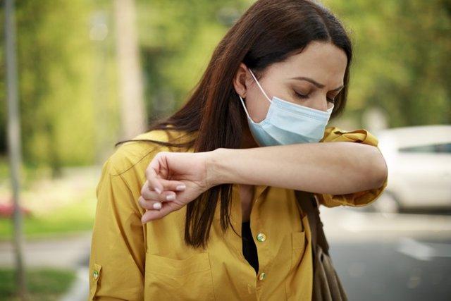Archivo - Mujer estornudando con mascarillla. Alergia. Primavera