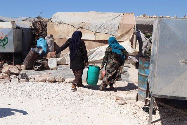 Mujeres desplazadas cargan un bidón de agua proporcionado por MSF en el noroeste de Siria