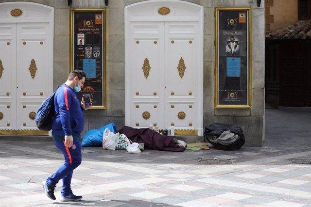 Archivo - Una persona sintecho duerme en la calle Arenal de la capital.
