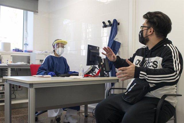 Archivo - Una trabajadora sanitaria atiende a un paciente en una de las consultas del CAP Masdevall el día en el que comienza la campaña de vacunación antigripal en la región, en Figueres, Girona (Catalunya), a 16 de octubre de 2020.La campaña coincide co