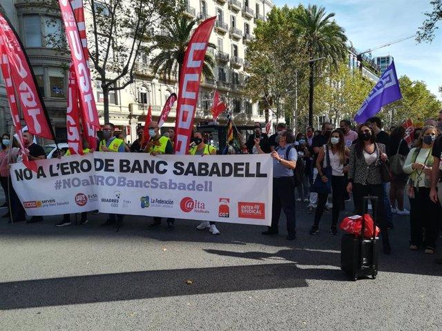 Un grupo de personas con una pancarta durante la protesta contra el ERE de Banco Sabadell ante su sede en la avenida Diagonal de Barcelona