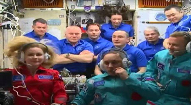 Yulia Peresid, primera actriz en el espacio, ataviada con un mono rojo.  Klim Shipenko está en primer plano a la derecha.