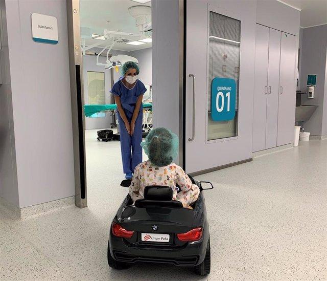 La doctora Jiménez con una paciente que conduce un cochecito hasta la entrada a quirófano.