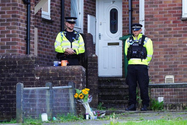 Archivo - 16 August 2021, United Kingdom, Plymouth: Police officers stand near floral tributes left outside 17 Biddick Drive in the Keyham area of Plymouth, where five people were killed by gunman Jake Davison in a firearms incident on Thursday evening. P