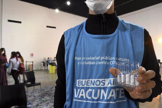 Archivo - Empleado de la campaña de vacunación en Argentina muestra viales de la vacunacontra la COVID-19