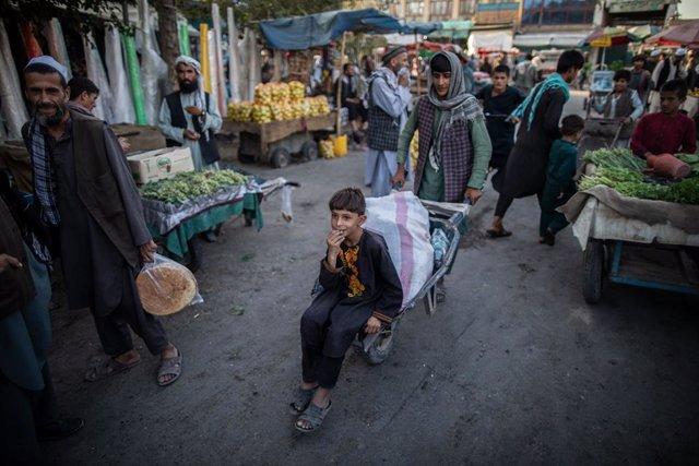 17 September 2021, Afghanistan, Kunduz: An Afghani boy rides a wheelbarrow in a market in Kunduz, northern Afghanistan. Photo: Oliver Weiken/dpa
