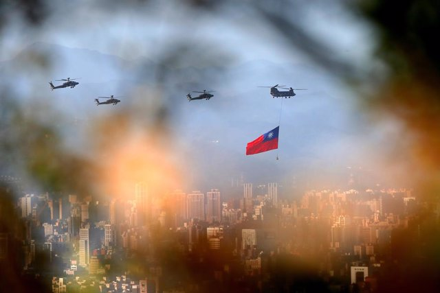 05 October 2021, Taiwan, New Taipei City: A military helicopter carrying a tremendous Taiwan flag conducts a flyby rehearsal with other helicopters ahead of the Double-tenth National Day celebration, near Taipei 101, amid China's growing military threats.