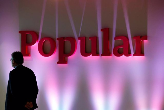 Archivo - FILE PHOTO: A man stands next to the logo of Spain's Banco Popular during the bank's results presentation in Madrid