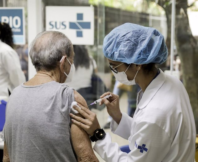 13 September 2021, Brazil, Rio de Janeiro: A health worker gives a coronavirus vaccine to an elderly woman third dose, as part of the third dose vaccination campaign for the elderly over 95 years old, at CMS Joao Barros Barreto hospital. Photo: Gabriel de