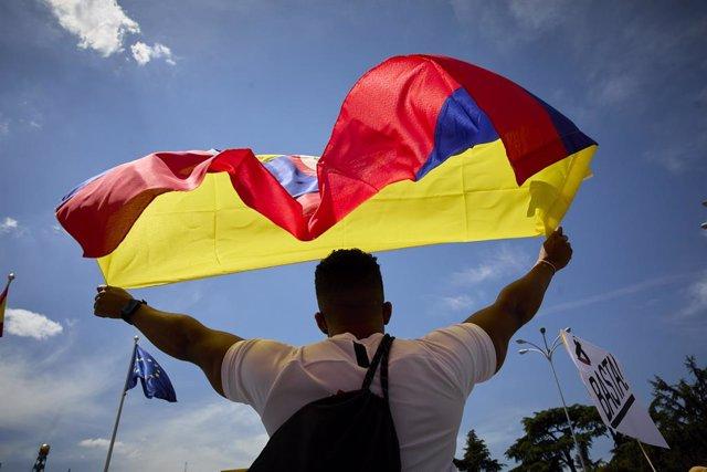 Archivo - Un hombre ondea una bandera de Colombia durante una nueva manifestación de apoyo al pueblo colombiano frente a la Puerta de Alcalá, a 8 de mayo de 2021, en Madrid (España). Esta protesta en la capital se suma a las convocadas en distintos puntos