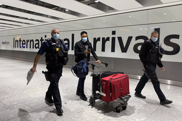 Archivo - 18 January 2021, United Kingdom, London: A passenger walks with police officers as he pushes a trolley through the arrival hall of Terminal 5 at London's Heathrow Airport, passengers arriving from anywhere outside the UK must have proof of a neg