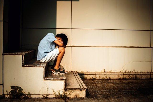 Archivo - Niño sentado en una escalera, triste, deprimido.