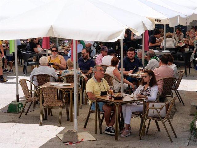 Archivo - Varias personas en la terraza de un restaurante en Galicia.