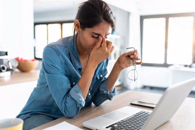 Mujer cansada delante de un ordenador.