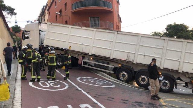 Bombers de Barcelona i la grua de Transports Metropolitans de Barcelona treballen per retirar el camió articulat