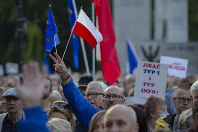 Archivo - 10 August 2021, Poland, Warsaw: A man gestures a victory sign while holding flags of Poland and the European Union during a protest in front of the Polish Parliament (Sejm) as part of a nationwide protest against a proposed bill by the lawmakers