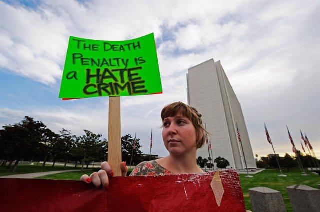 Archivo - Una manifestante contra la pena de muerte sostiene un cartel durante una protesta en Los Ángeles.