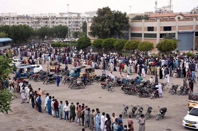 Archivo - Un grupo de personas hace cola para recibir la vacuna contra el coronavirus en Pakistán