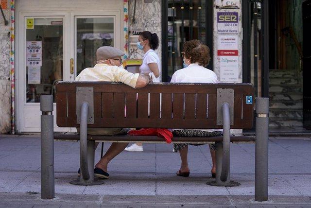 Archivo - Una pareja de ancianos con mascarilla sentada en un banco, a 27 de julio de 2021, en Madrid, (España).