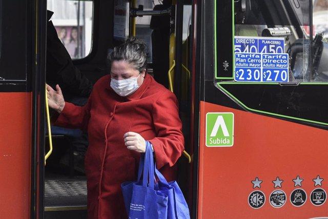 Archivo - Una mujer con mascarilla baja de un autobús en Viña del Mar