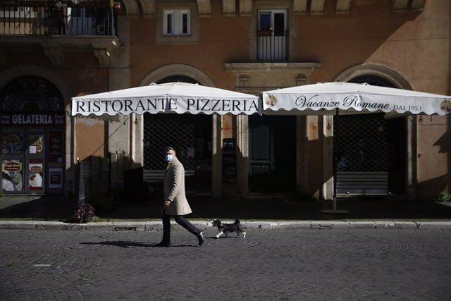 Archivo - 15 March 2021, Italy, Rome: A man walks his dog on an empty street amid newly reimposed restrictions to curb the spreading of coronavirus. Photo: Cecilia Fabiano/LaPresse via ZUMA Press/dpa