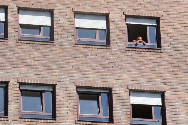 Archivo - Una persona mayor se asoma a la ventana de su habitación, en una residencia de Lugo.
