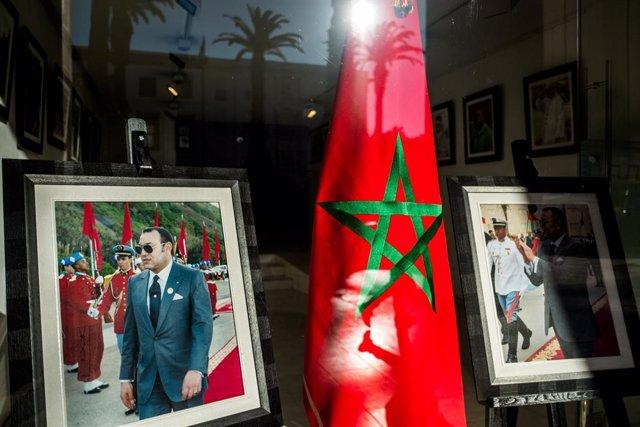 Archivo - Una bandera de Marruecos y una fotografía del rey Mohamed VI en un escaparate en Rabat