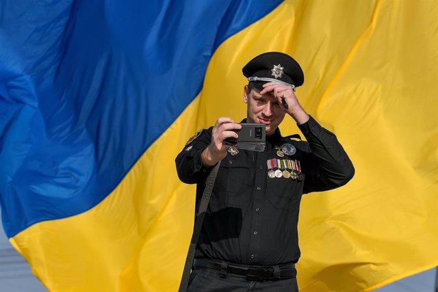 Archivo - 23 August 2019, Ukraine, Zaporizhzhia: A police officer takes a selfie in front of a Ukrainian flag during the flag-hoisting ceremony, part of National Flag Day celebration, on Khortytsia Island. Photo: -/Ukrinform/dpa
