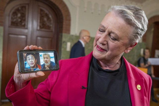 08 October 2021, Norway, Oslo: The chairman of the Norwegian Nobel Peace Prize Committee, Berit Reiss-Andersen, shows a picture of this year's Peace Prize winners, journalists Maria Ressa and Dmitry Muratov during the announcement of the Nobel Peace Prize
