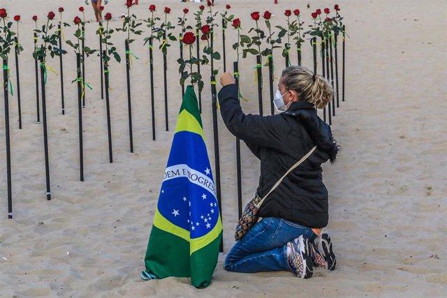 Archivo - Una mujer coloca una rosa durante una protesta de activistas de la ONG Río de Paz en la playa de Copacabana por la gestión de la pandemia en el país.