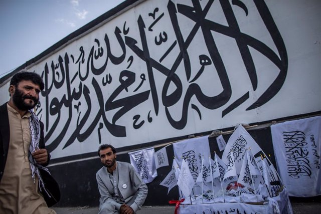 24 September 2021, Afghanistan, Kabul: An Afghan man sells Taliban flags backdropped by the Muslim creed written on a wall of the former United States embassy in Kabul. Photo: Oliver Weiken/dpa
