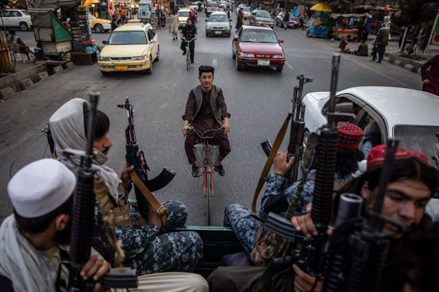 22 September 2021, Afghanistan, Kabul: An Afghan man rides a bicycle as young Taliban fighters patrol the streets of Kabul on the back of a pick up truck. Photo: Oliver Weiken/dpa