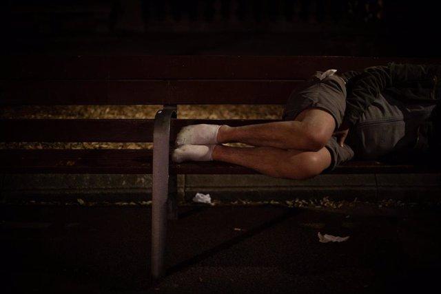 Archivo - Un hombre duerme sobre un banco en la Plaza de Catalunya, en Barcelona.