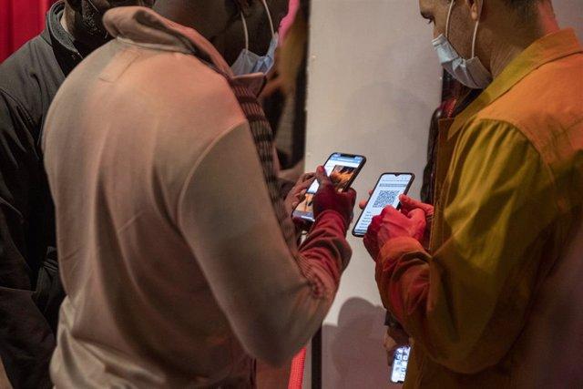 Una persona mostra un codi QR per entrar a un local d'oci nocturn el dijous