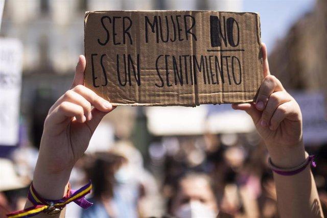 Archivo - Una mujer sujeta un cartel en el que se lee: `Ser mujer no es un sentimiento, durante una manifestación contra la Ley Trans del Igualdad, en Madrid.