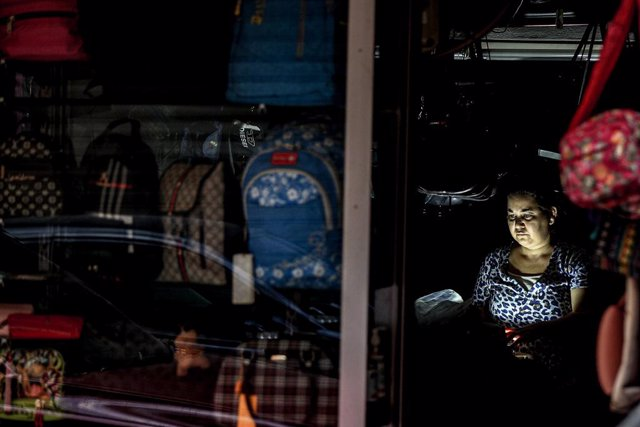 24 September 2021, Lebanon, Beirut: A Lebanese woman sits inside a suitcases shop during an electricity outage. Photo: Marwan Naamani/dpa