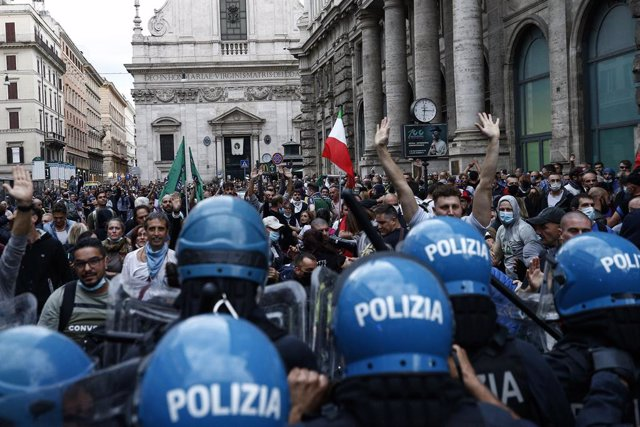 09 October 2021, Italy, Rome: Protesters and police officers clash during a demonstration against the Corona health pass. Italian workers in the public and private sectors will have to show a health passport to enter their workplace from 15 October. Photo