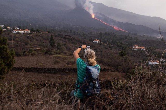 Un hombre toma una foto del volcán de Cumbre Vieja en La Palma cuando vuelve a expulsar lava y piroclastos tras horas de relativa inactividad, a 27 de septiembre en Tacande de Abajo, El Paso, La Palma, Santa Cruz de Tenerife, Canarias (España).