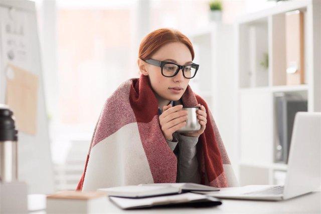 Archivo - Mujer con frío en la oficina.