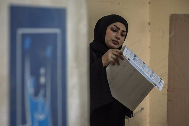 10 October 2021, Iraq, Baghdad: An Iraqi woman checks the list of candidates at a polling station in the Habibiya neighbourhood, before casting her vote during the Iraqi parliamentary elections. Photo: Ameer Al Mohammedaw/dpa