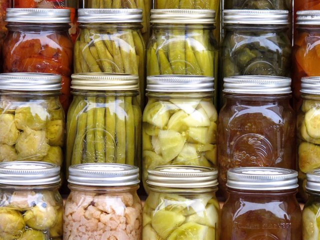 Pickled vegetables including carrots, green beans, tomatoes, and cauliflower are on display at a farmerâ market during the Derby Day Wine and Whiskey Walk event.
