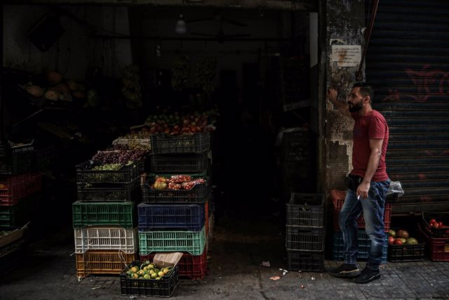 24 September 2021, Lebanon, Beirut: A vendor stands outside a grocery shop during an electricity outage. Photo: Marwan Naamani/dpa