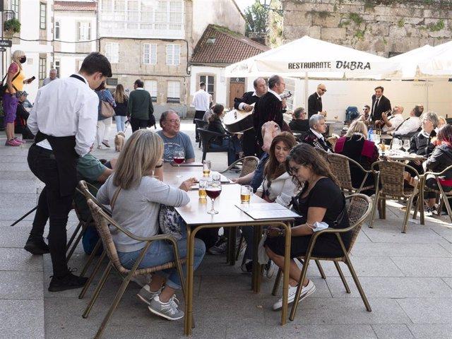 Un grupo de turistas consulta una carta en la terraza de un bar en Santiago de Compostela.