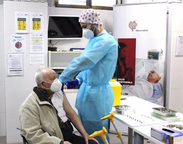 Archivo - Un profesional de Ribera vacuna a un anciano