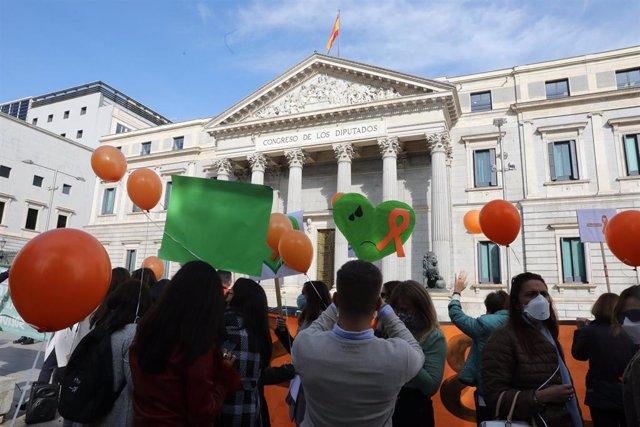 Archivo - Varias personas portan globos naranjas durante una concentración convocada ante el Congreso contra la LOMLOE, la reforma de la ley educativa conocida como 'ley Celaá', en Madrid.