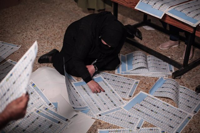 10 October 2021, Iraq, Baghdad: An Iraqi election committee staff member counts the votes for the Iraqi parliamentary elections, at a polling station in Baghdad's Karada district. Photo: Ameer Al Mohammedaw/dpa
